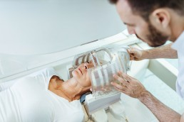 A patient is prepped for an MRI early-onset Alzheimer's test by a medical technician